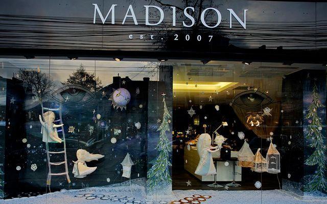 Diseño y decoración de navidad en colores blancos para los escaparates de las tiendas